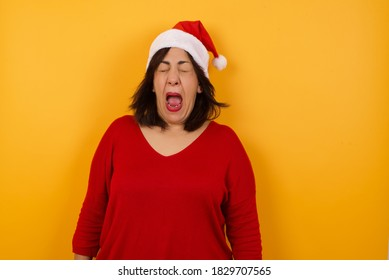 Stressful middle aged woman wearing Christmas hat, screams in panic, closes eyes in terror, keeps hands on head, finds out terrified news or disaster about best friend, can't believe it.