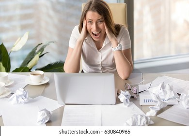 Stressful young businesswoman shouting at desk with laptop. Female entrepreneur suffers from nervous breakdown caused by fatigue, too much hard work. Woman feels sudden attack of headache at workplace