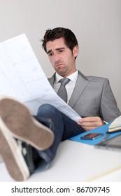 Stressless businessman looking at construction plan