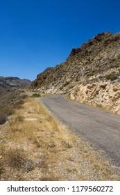 Stretch of bendy road in desertic Andalusian landscape in Nijar, province of Almeria, Spain.