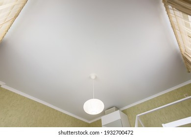 Stretch white matte ceiling close-up in the interior of a bedroom