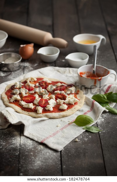 Stretched and uncooked pizza dough with tomato sauce, mozzarella and cherry tomatoes on a kitchen towel. Taken on a rustic dark table with flour, rolling pin, salt, oregano, egg and fresh basil.