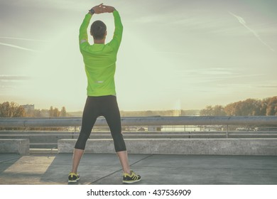 Stretching after jogging on a bridge.