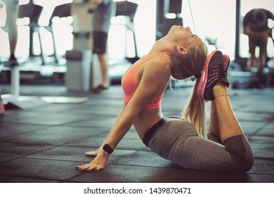 Stretching allows you to do much more while working out. Woman at gym.