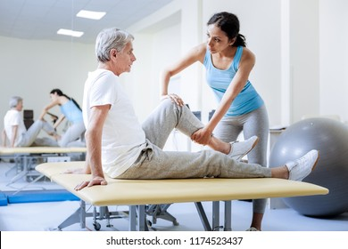 Stretching. Attentive responsible calm medical worker being careful while warming the injured muscles of a worried aged patient in the rehabilitation center