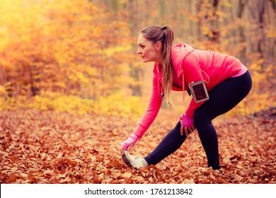 Estiramiento y ejercicio. Joven deportista encajonada haciendo deportes al aire libre. Una mujer positiva pasa tiempo en el aire fresco en el bosque otoñal.