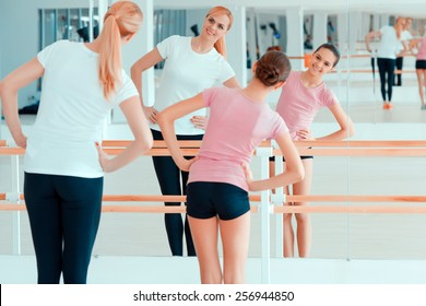 Stretching is a great start of the day. Beautiful mature woman and her teenage daughter in sports clothing warming up before the workout while standing against mirror in health club