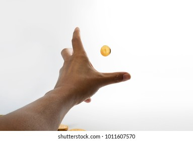 Stretching hands to grab gold coin first person point of view