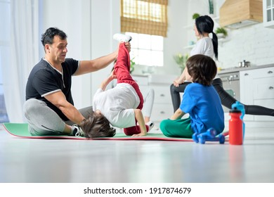 Stretching at home. Two little boys having fun, practicing yoga on a mat with father while their mom and sister exercising in the background