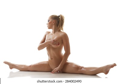 Stretching. Nude sweaty girl doing gymnastic split