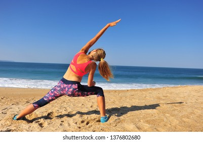 Stretching on the beach, athletic woman