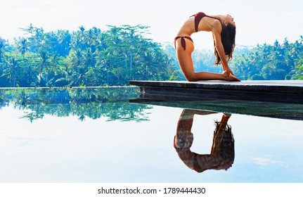 Stretching on sunrise background. Active woman in bikini practicing yoga at villa poolside to keep fit and health. Stand in ustrasana camel pose. Woman fitness, sport activity on summer family holiday