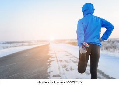 Stretching Running - woman runner doing exercises. Winter marathon