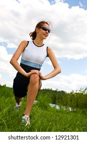 A stretching woman in front of cross country