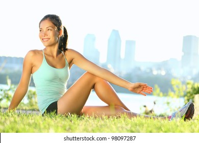 Stretching woman in outdoor exercise smiling happy doing yoga stretches after running. Beautiful happy smiling sport fitness model outside on summer / spring day.