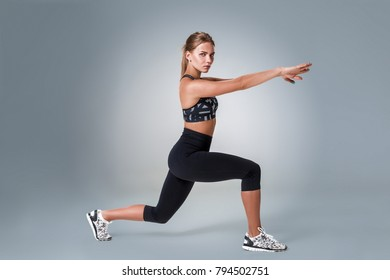 Stretching workout posture by a woman on studio gray background