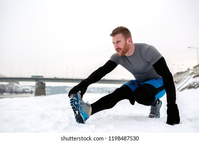Stretching and worming up before workout on the snowy runway near the river