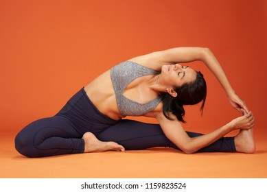 Stretching yoga asana pose woman show on orange color studio background