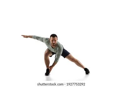 Stretching. Young caucasian male model in action, motion isolated on white background with copyspace. Concept of sport, movement, energy and dynamic, healthy lifestyle. Training, practicing. Authentic