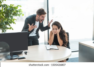 strict boss man swearing at depressed employee woman for bad work at the workplace looking angry