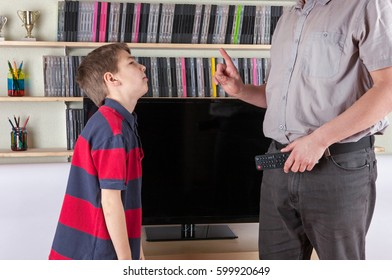 Strict dad holding the remote control not allowing watching the TV for his son