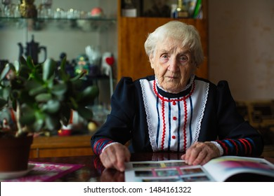 Strict elderly woman in Slavic clothes sitting reading a magazine.