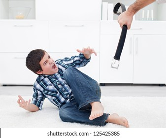 Strict father punishing his son with a belt