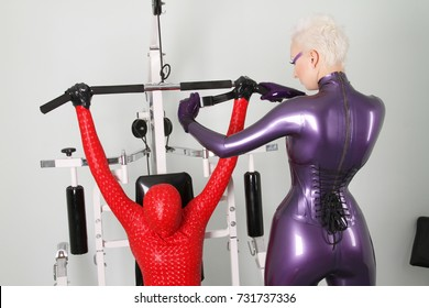 strict kinky mistress and two her bdsm zentai slaves in the white gym