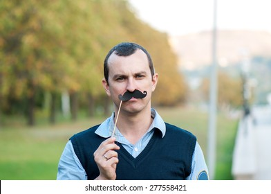 strict man with decorative moustaches on a stick looks in the camera