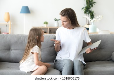 Strict mother scolding little daughter for long laptop use, angry woman with preschool girl sitting on couch in living room, holding computer in hands, parent reprimanding, lecturing child