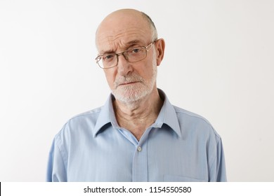 Strict senior male teacher wearing rectangular spectacles and blue shirt frowning feeling angry at his misbehaving students, posing against white studio wall background with copy space for your text