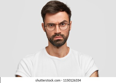 Strict serious discontent male boss raises eyebrows with angry displeased expression, dislikes something, expresses negative emotions, dressed casually, poses against white studio background.