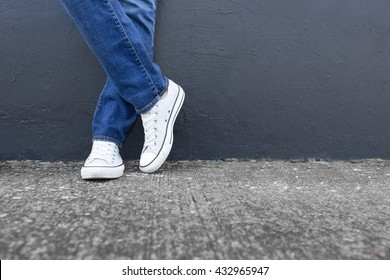 Strike a pose. Person in jeans and shoes posing up against a wall.