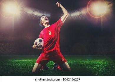 striker soccer football player in red team concept celebrating goal in the dark contrast stadium