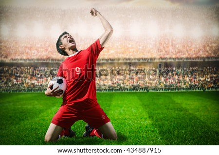 striker soccer football player in red team concept celebrating goal in the stadium during match