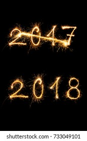 Strikethrough 2017 and 2018 digits made of sparkling light isolated on black background. Old year going, new year comming. PF2018
