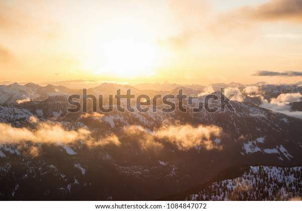 Striking and beautiful aerial landscape view of Canadian Mountains during a vibrant sunsetd. Taken North of Vancouver, British Columbia, Canada.