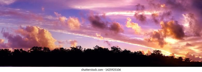 A striking brightly coloured orange cumulonimbus cloudy tropical panoramic sunset cloudscape featuring horizon in silhouette. Queensland, Australia.