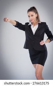 Striking executive woman in a business suit punching the air. Posed in a studio background.
