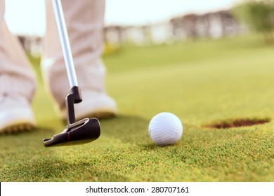 Striking it gently Close up of man going to putt ball into hole with help of golf club