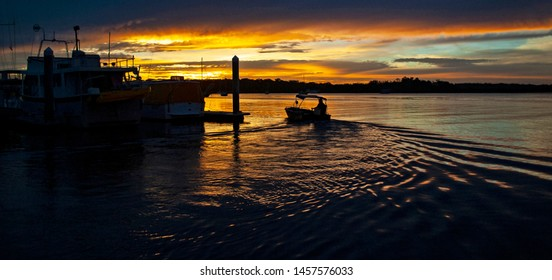 A striking inspirational golden colored cloudy marina/dock sunset seascape over sea water with water reflections and a boat in silhouette.Captured in Tin Can Bay, Queensland, Australia.