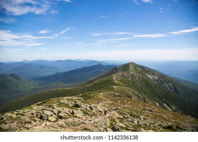 Striking landscape photography of stunning mountain ranges along the Appalachian trail on a beautiful blue sky and sunny day. Views from Franconia Ridge Loop, Mount Lafayette traverse nature trail