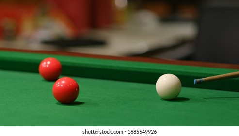 Striking snooker ball on table