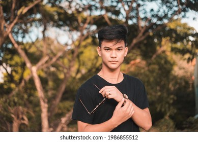 A strikingly handsome young Filipino man at the park. In a black t-shirt. At the park during late afternoon.