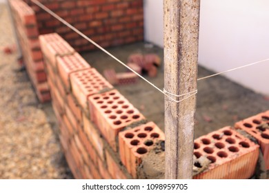 string being used as a level in the construction of a wall of a small brick building
