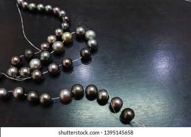 String of Black pearl necklace on the black wood table