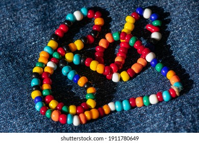String of colorful seed beads on a denim background