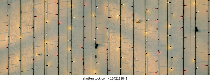 String lights hang on wooden wall.