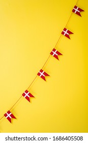 A string of little wooden Danish flags (Dannebrog) against a bright yellow background.