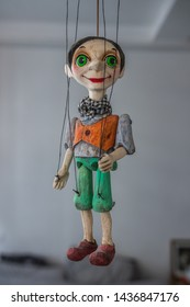 String operated puppet (marionette) from Prague (Czech Republic). Beautiful close up of this strange looking tiny person. It is hanging in the air. Wearing a scarf, short hair, has big green eyes.